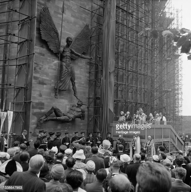 Crowd of people watching the unveiling ceremony of the statue St Michael and the Devil by sculptor Jacob Epstein at Coventry Cathedral. The statue of...