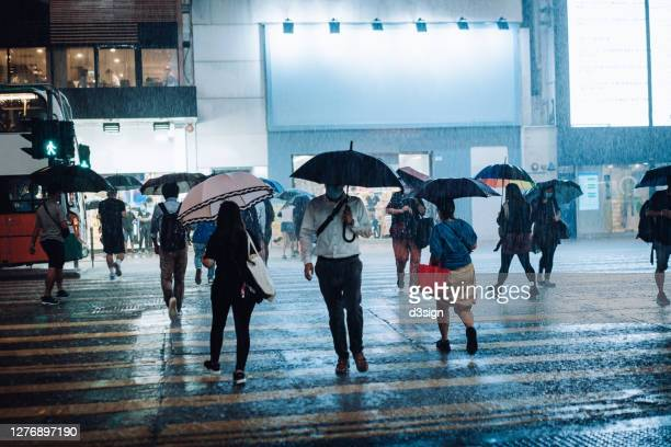 crowd of people with protective face mask carrying umbrellas crossing the street in downtown district in the city, against the reflection of glowing neon lights and city buildings in heavy rain at night - 集中豪雨 ストックフォトと画像