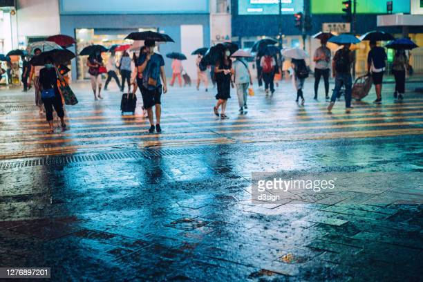 crowd of people with protective face mask carrying umbrellas crossing the street in downtown district in the city, against the reflection of glowing neon lights and city buildings in heavy rain at night - torrential rain stock pictures, royalty-free photos & images