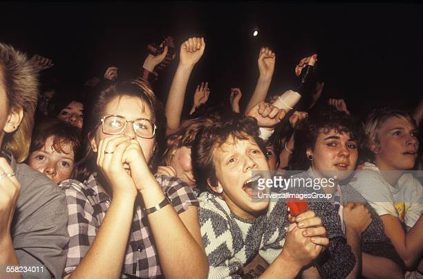 A crowd of pop music fans cheering at a stage UK 1980s