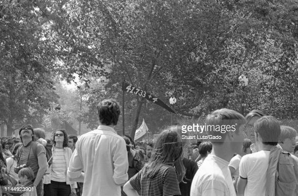 "Crowd of protestors, one holding a banner with the text ""41, 733 plus 4, "" referencing the death counts in Vietnam and Kent State, during the Kent..."