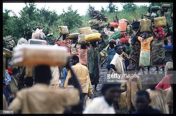 Crowd of refugees carry their belongings May 3, 1994 at the border of Rwanda and Tanzania. Hutu refugees have fled to Tanzania border across the...