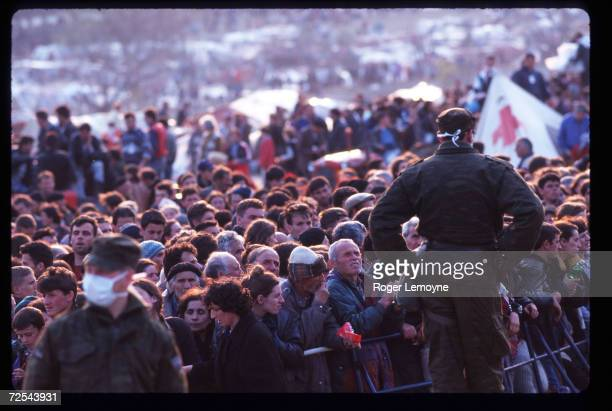 A crowd of refugees stands behind a fence April 1 1999 in Macedonia Thousands of Kosovar Albanians fled the violence in Serbia and arrived at Blace a...