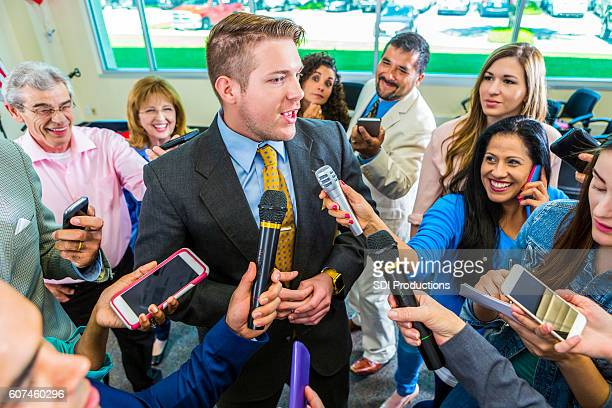 Crowd of reporters interview mid adult male politician