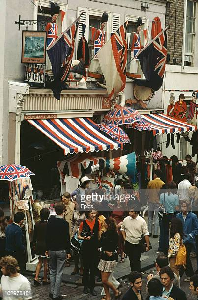 A crowd of shoppers on Portobello Road market London August 1970 The antiques shop 'Georgian House' displays flags and Union Jack umbrellas outside