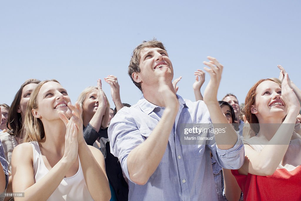 Crowd of smiling people clapping and looking up : Stock Photo