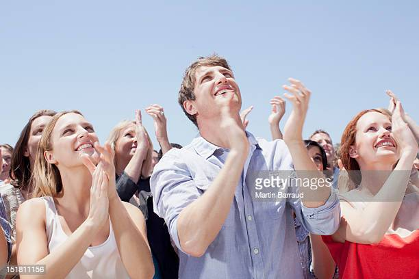Crowd of smiling people clapping and looking up
