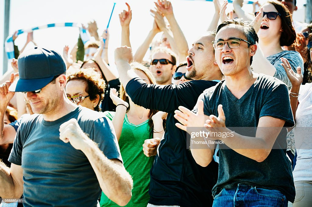 Crowd of soccer fans celebrating during match : Stock Photo