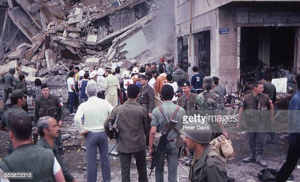 A crowd of soldiers and aid givers stand amid the destruction and damage at the scene of the suicide bombing of the American Embassy Beirut Lebanon...