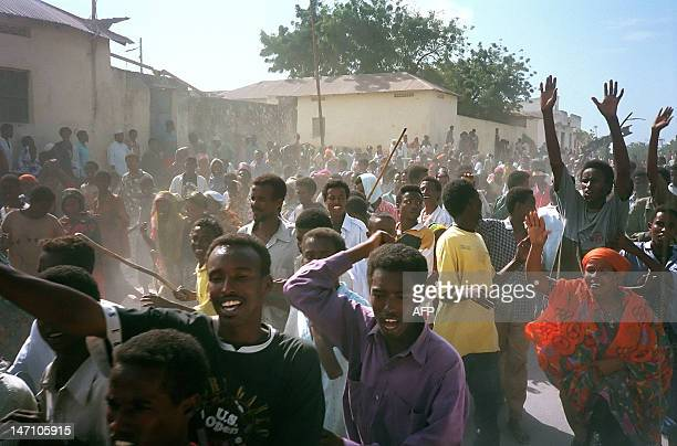 A crowd of Somalis gestures in the streets of Mogadishu as the body of a US soldier killed 03 October 1993 is displayed through the streets 04...