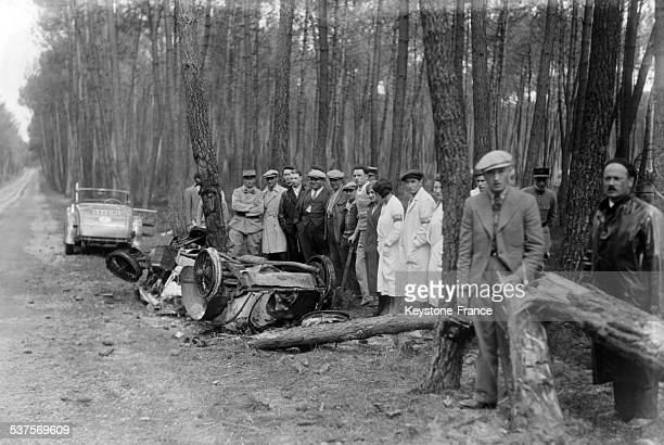 A crowd of spectators around the debris of the car of Mrs Siko competitor in the 24 Hours of Le Mans race unscathed from an accident that completely...