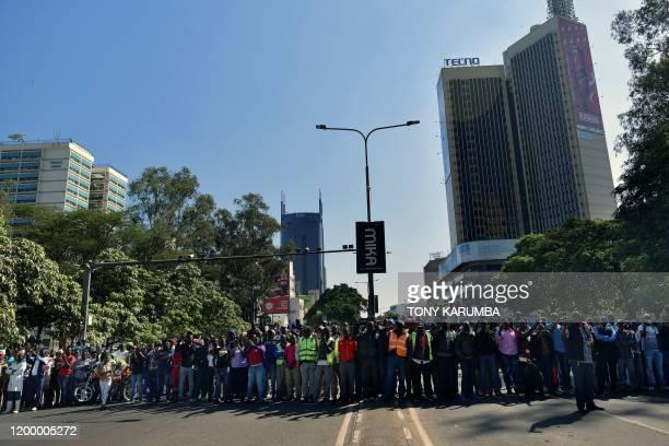 A crowd of spectators gather on Kenyatta avenue to watch as the flagdraped casket bearing the body of Kenya's former president Daniel arap Moi goes...
