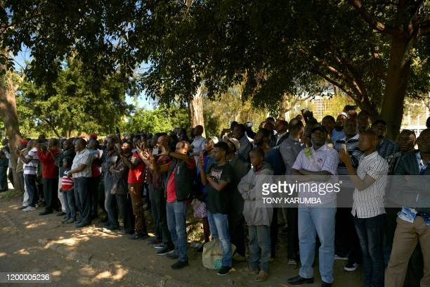 A crowd of spectators gather to watch as the flagdraped casket bearing the body of Kenya's former president Daniel arap Moi goes past in a military...