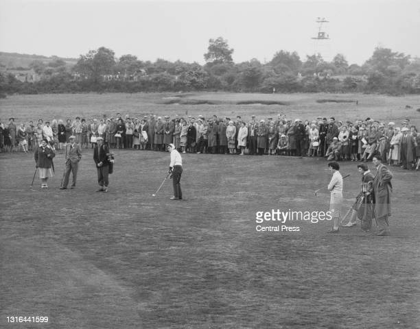 Crowd of spectators watch as Anne Quast of the United States chips off the fairway to the 12th green during her singles match against Janette...