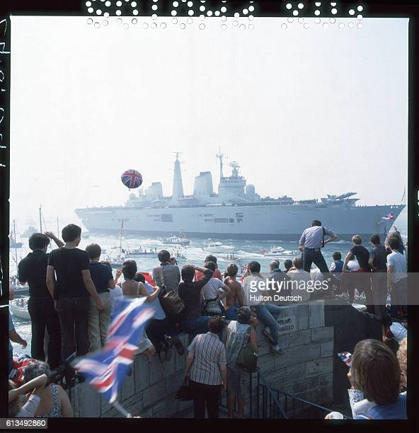 A crowd of spectators watches the warship HMS Invincible after her return from the Falklands War