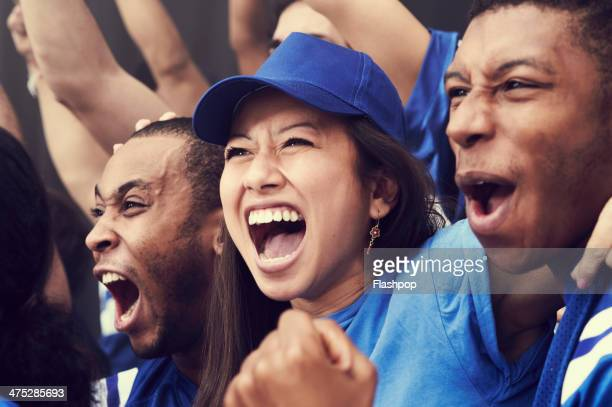 crowd of sports fans cheering - cheering ストックフォトと画像