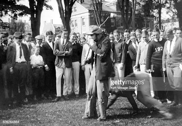 A crowd of students gather to watch what appears to be a hazing prank on the campus of Dartmouth College in the 1920s