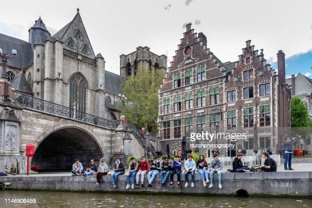 ゲントの歴史的中心部に graslei 堤防の川岸に座っている学生の群衆 - ベルギー ゲント ストックフォトと画像