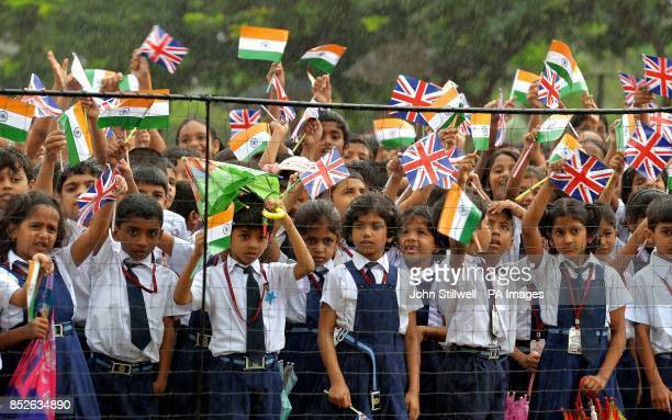 A crowd of students wait in the pouring rain to see the Duchess of Cornwall at the Rajagiri Public School in Kochi south west India on the seventh...