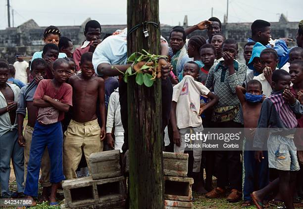 A crowd of teenagers and children observe the slumped body of a young Armed Forces of Liberia soldier accused of looting and murder who has just been...