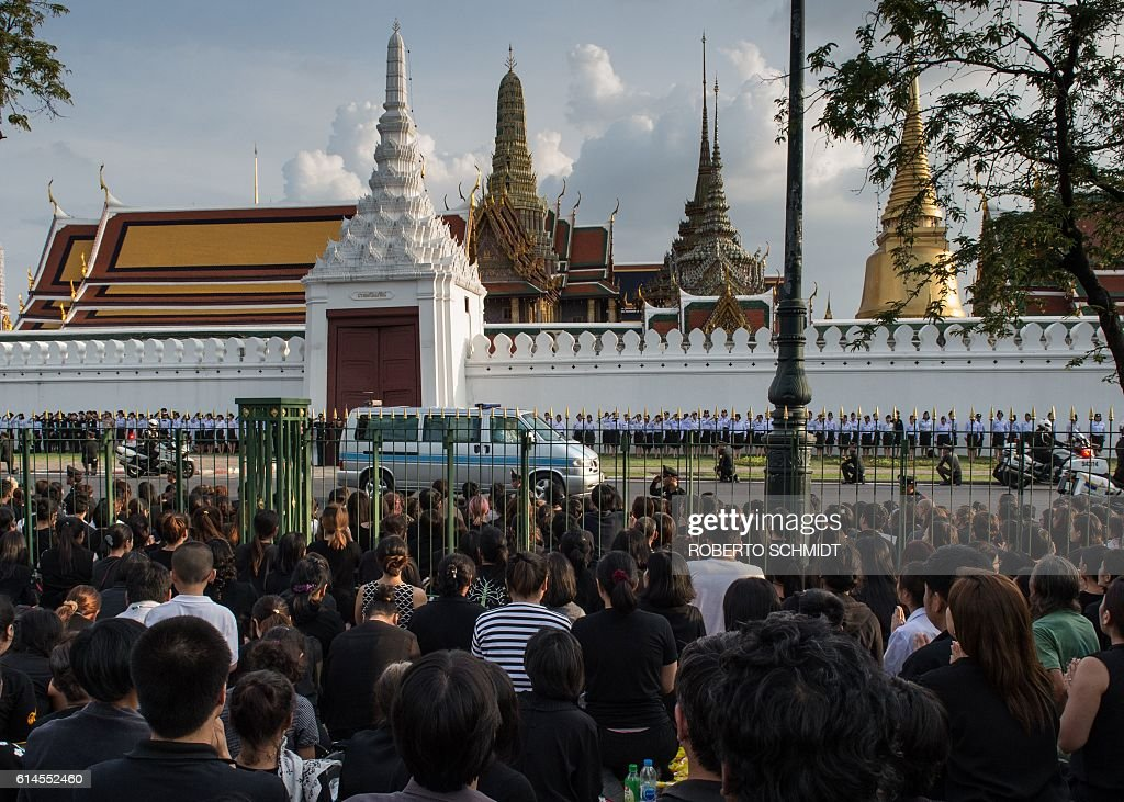 A crowd of Thais watch in total silence the van carrying the body of Thailand's King Bhumibol Adulyadej as a funeral caravan reached the Thai Royal Palace on October 14, 2016. Bhumibol, the world's longest-reigning monarch, passed away aged 88 on October 13, 2016 after years of ill health, removing a stabilising father figure from a country where political tensions remain two years after a military coup. / AFP / ROBERTO