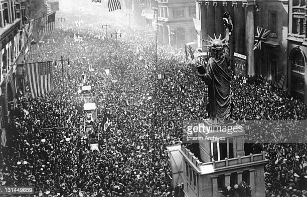 Crowd of thousands massed on Broad Street near a replica of the Statue of Liberty, to cheer as news of the armistice was announced to the public,...