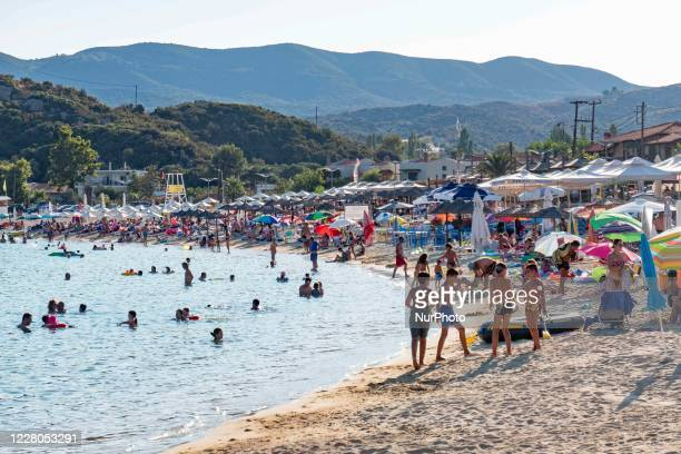 Crowd of tourists at the popular and famous beach of Kalamitsi located on the southern tip of Sithonia peninsula in Chalkidiki in Northern Greece....