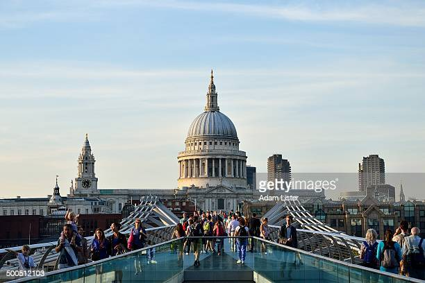 Crowd of tourists cross the Millennium Bridge in London with the sunlit St Pauls behind.