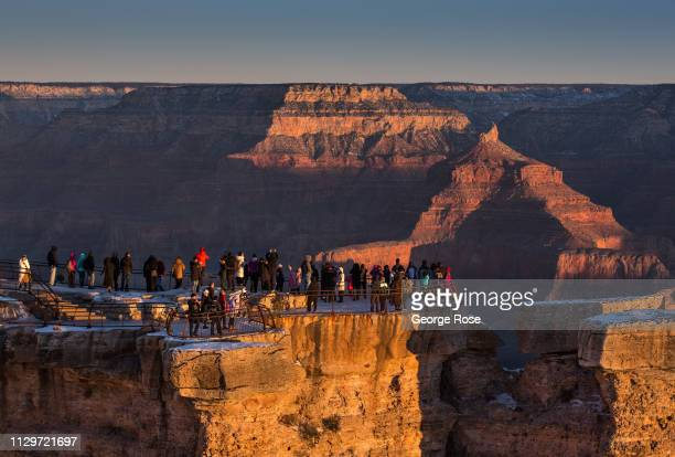 A crowd of tourists gather at Mather Point Lookout located on the South Rim to watch the sunrise on February 8 in Grand Canyon National Park Arizona...