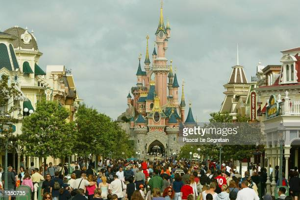 Crowd of tourists walk toward the Sleeping Beauty castle on main street at Disneyland Paris August 22, 2002 in Marne la Vallee, France. After a rocky...