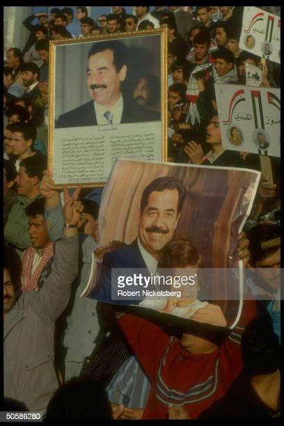 Crowd of veed fingerraising Palestinians w portraits of Iraqi Pres Saddam Hussein holding proIraqi antiUS gulf crisis demo
