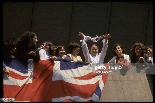 Crowd of wellwishers w. Union Jack draped on dock as Army wife holds out bra to entertain troops sailing to Falklands on QE2