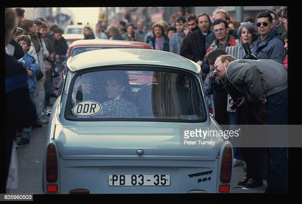 A crowd of West Germans welcome the first travelers from the east since reunification of the country