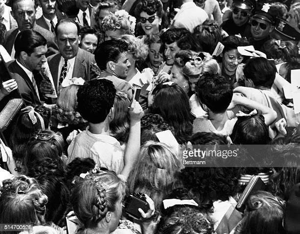 Crowd of women, autograph books in hand, presses against a young Frank Sinatra.