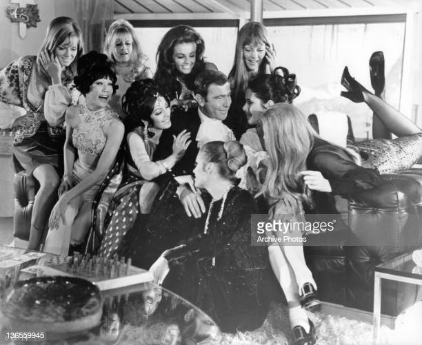A crowd of women happily give George Lazenby their undivided attention and affection in a scene from the film 'On Her Majesty's Secret Service' 1969