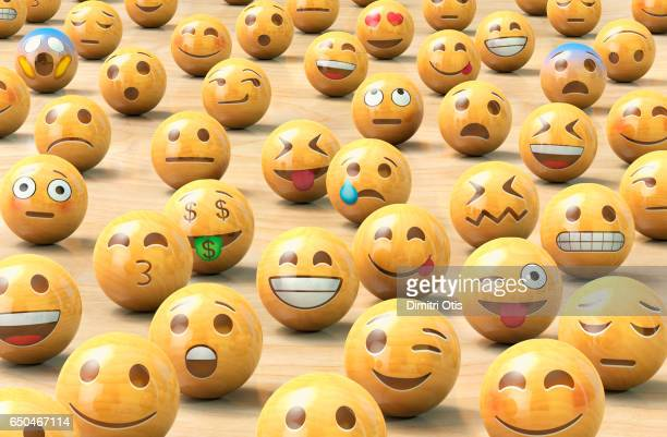A crowd of wooden emoticon or Emoji face balls