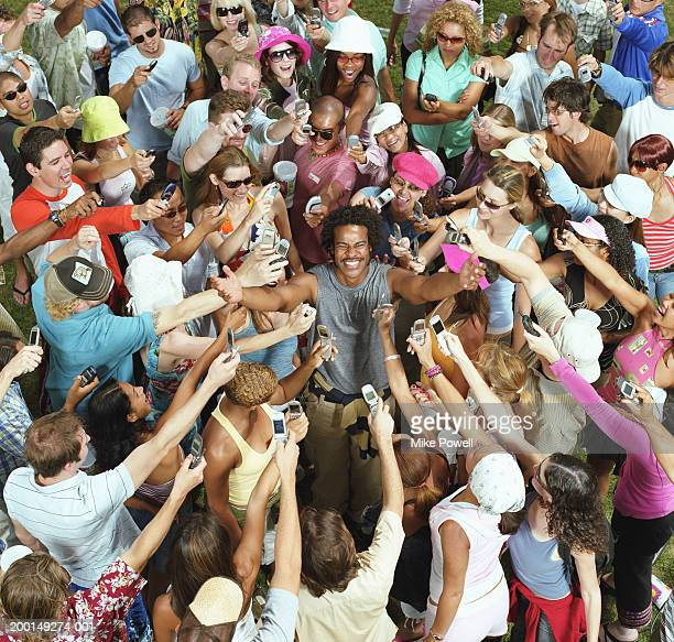 crowd of young adults taking photos of man with mobile phones - adulation stock pictures, royalty-free photos & images