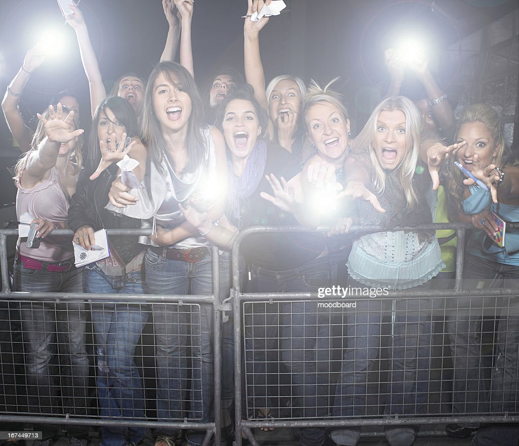 Crowd of young female fans screaming and cheering at concert : Stock Photo