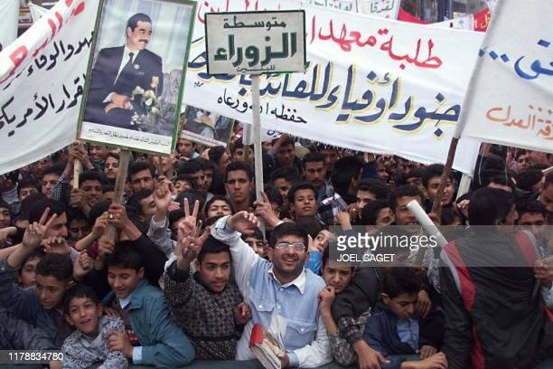 A crowd of young Iraqi hold banners and a picture of Saddam Hussein 16 January in the streets of Baghdad The protesters denounce the embargo imposed...