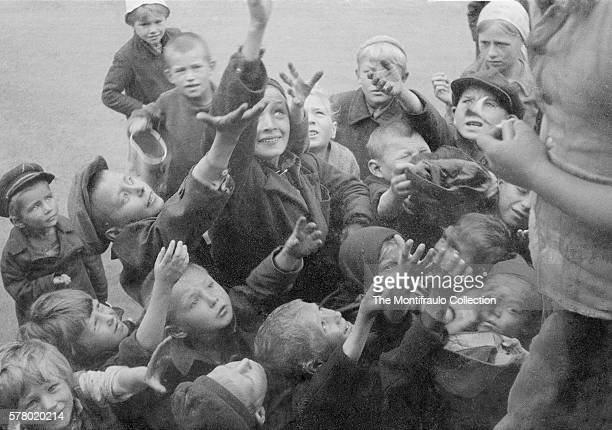 Crowd of young Russian children waiting to receive food being offered by a German soldier during World War II Eastern Front circa 1941