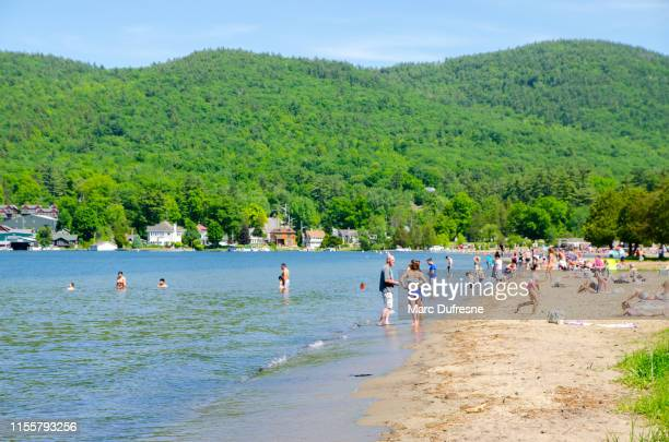 crowd on beach of lake george - lake george new york stock pictures, royalty-free photos & images