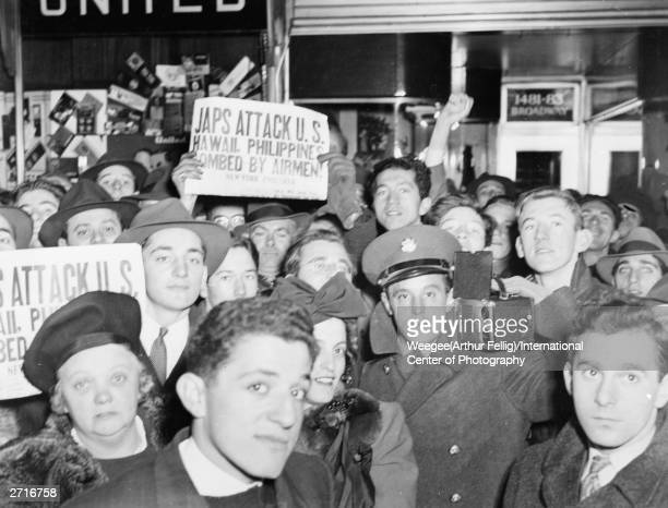 A crowd in Broadway New York hold up newspapers announcing the Japanese attack on Pearl Harbour Hawaii during World War II Photo by Weegee...