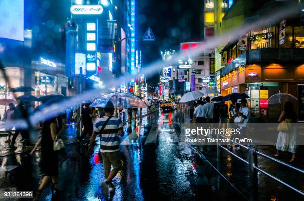 Crowd On City Street During Rainfall At Night