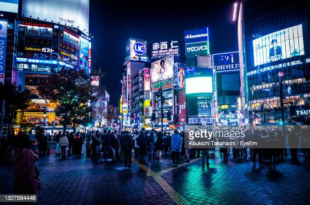 crowd on illuminated city at night in shibuya crossing tokyo japan - koukichi stock pictures, royalty-free photos & images