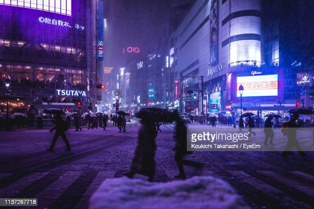 Crowd On Snow Covered Street Amidst Illuminated City At Night