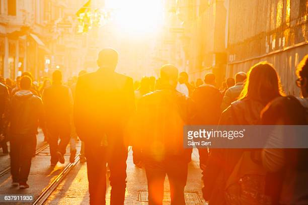 crowd on street in bright lens flare - religion stock-fotos und bilder
