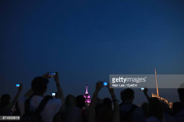 Crowd Photographing Illuminated Empire State Building At Night Against Clear Blue Sky
