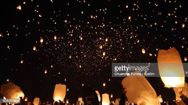 crowd releasing illuminated paper lanterns at night - releasing stock pictures, royalty-free photos & images