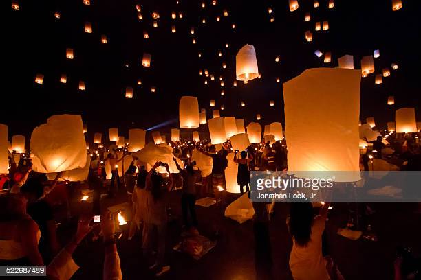 crowd releasing lanterns into sky - lantern festival stock photos and pictures
