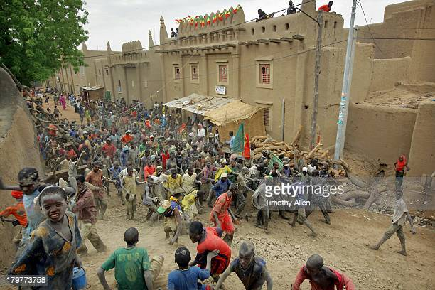 crowd runs through street in djenne, mali - djenne grand mosque stock pictures, royalty-free photos & images